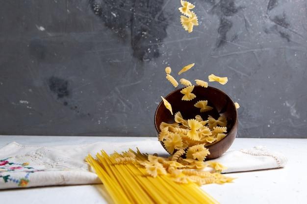 Widok z przodu surowy włoski makaron długi i mały miskę makaronu