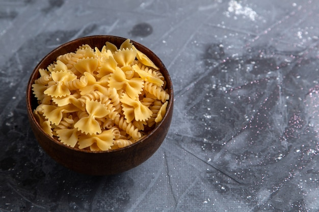 Widok z przodu surowy włoski makaron trochę uformowany wewnątrz brązowej tablicy na szarym stole makaron włoski posiłek żywności