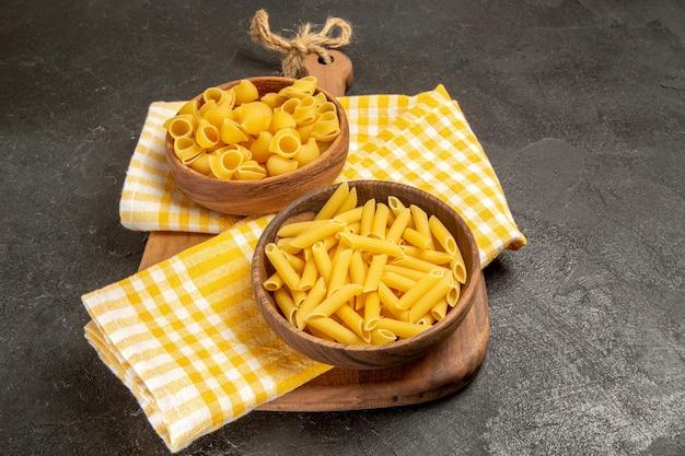 Widok z przodu surowy włoski makaron wewnątrz brązowych talerzy na szarej przestrzeni
