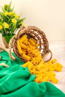 Widok z przodu surowy włoski makaron żółty wewnątrz koszyczka wraz z linami na zielonej tkance