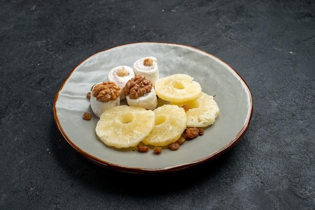 Widok z przodu suszone krążki ananasa z rodzynkami wewnątrz talerza na szarej powierzchni owoce suszone rodzynki słodkie zdjęcie