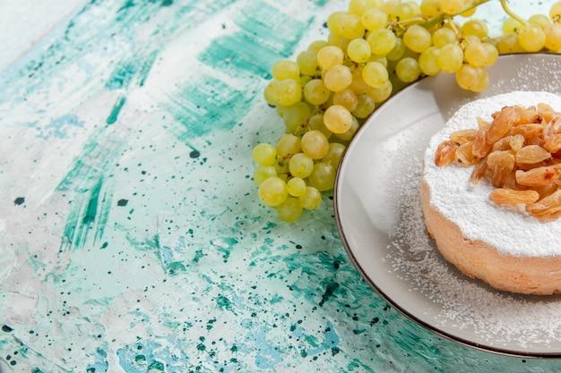 Widok z przodu suszone rodzynki z winogron ze świeżymi zielonymi winogronami i cukrem ciasto w proszku na niebieskiej powierzchni suszone rodzynki owoce kolor zdjęcie ciasto cukier
