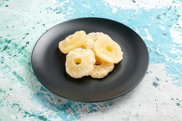 Widok z przodu suszonych krążków ananasa wewnątrz talerza na niebieskiej powierzchni