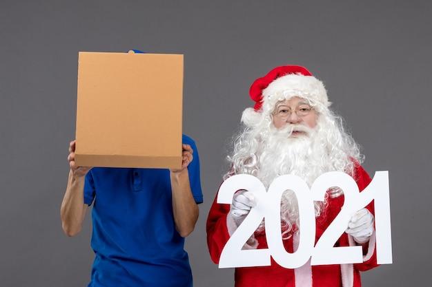 Widok z przodu świętego mikołaja z kurierem męskim trzymającym torby na zakupy i pudełko z jedzeniem na szarej ścianie