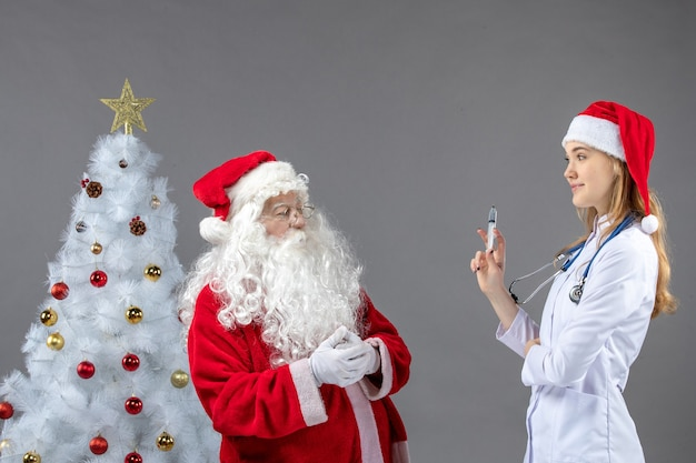 Widok z przodu świętego mikołaja z lekarką, która trzyma zastrzyk na szarej ścianie