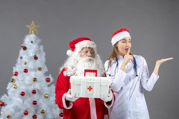 Widok z przodu świętego mikołaja z lekarką, która wręczyła mu apteczkę na szarej ścianie