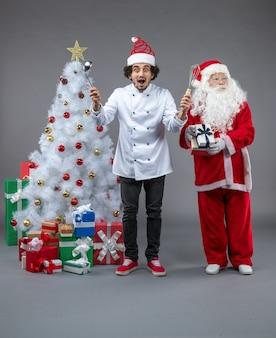 Widok z przodu świętego mikołaja z męskim kucharzem wokół prezentów świątecznych na szarej ścianie