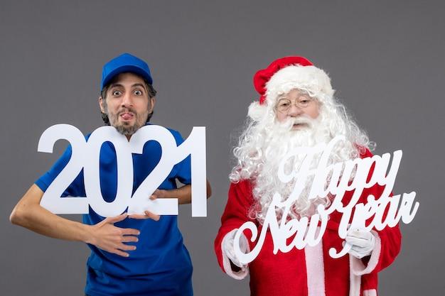 Widok z przodu świętego mikołaja z męskim kurierem trzymającym szczęśliwego nowego roku i tablice 2021 na szarej ścianie