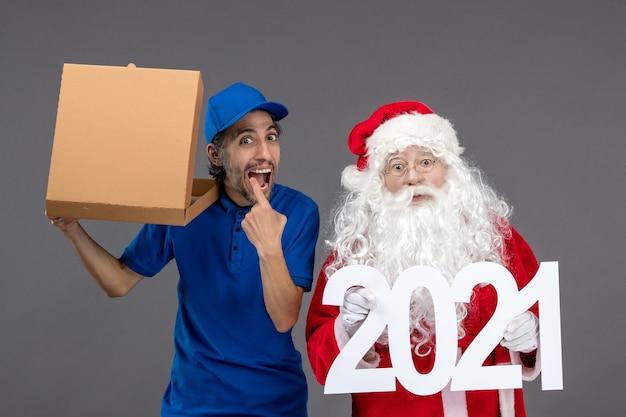 Widok z przodu świętego mikołaja z męskim kurierem trzymającym sztandar 2021 i pudełko z jedzeniem na szarej ścianie