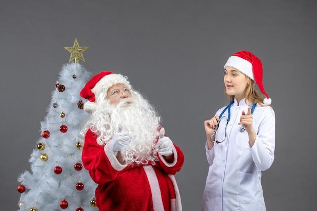 Widok z przodu świętego mikołaja z młodą kobietą lekarza na szarej ścianie