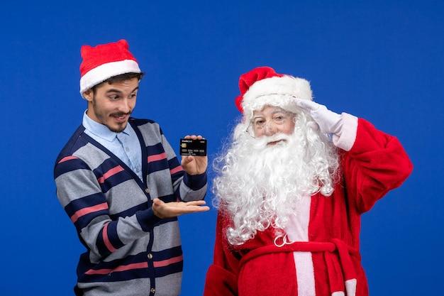 Widok z przodu świętego mikołaja z młodym mężczyzną trzymającym kartę bankową na niebieskiej ścianie