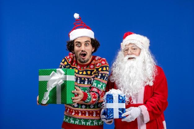 Widok z przodu świętego mikołaja z młodym mężczyzną trzymającym prezenty świąteczne na niebieskiej ścianie
