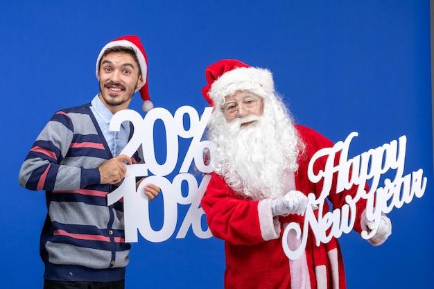 Widok z przodu świętego mikołaja z młodym mężczyzną trzymającym szczęśliwego nowego roku i napisy liczbowe na niebieskiej ścianie