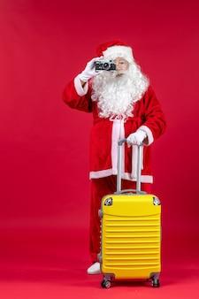 Widok z przodu świętego mikołaja z żółtą torbą robi zdjęcie aparatem na czerwonej ścianie