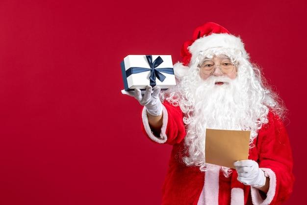 Widok z przodu święty mikołaj czytający list od dziecka i trzymający prezent na czerwonej podłodze emocja prezent świąteczny prezent