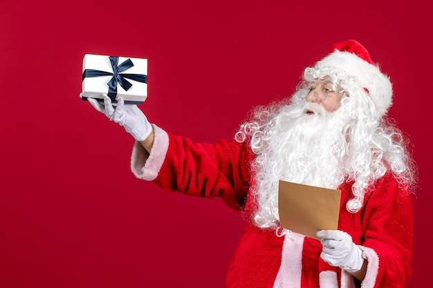 Widok z przodu święty mikołaj czytający list od dziecka i trzymający prezent na czerwonych emocjach prezent świąteczny