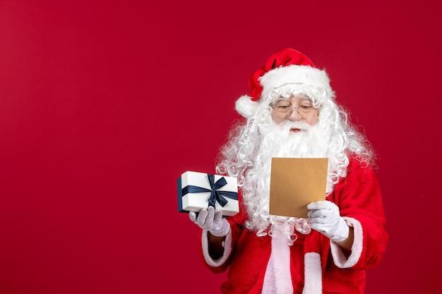 Widok z przodu święty mikołaj czytający list od dziecka i trzymający prezent na czerwonym świątecznym prezencie emocji
