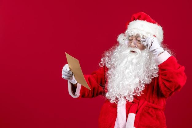 Widok z przodu święty mikołaj czytający list od dziecka na czerwonej podłodze świątecznych emocji świątecznych