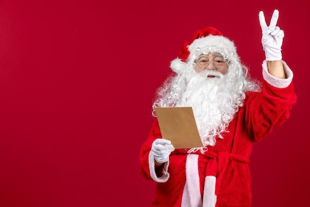 Widok z przodu święty mikołaj czytający list od dziecka na czerwonych emocjach prezent świąteczny