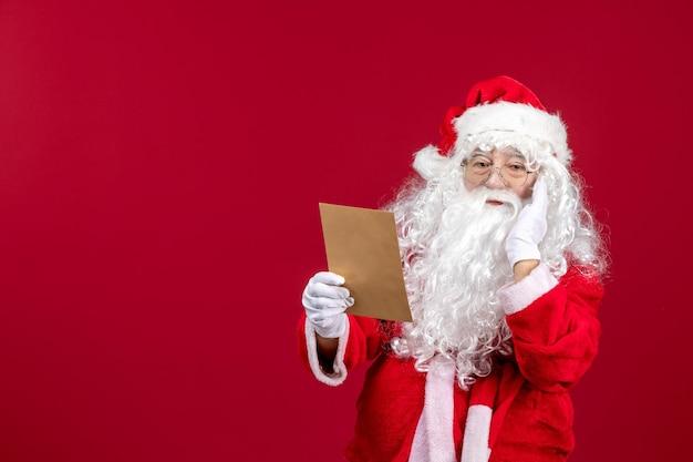 Widok z przodu święty mikołaj czytający list od dziecka na czerwonych emocjach przedstawia świąteczne wakacje