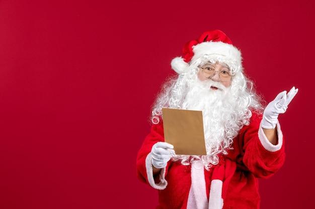 Widok z przodu święty mikołaj czytający list od dziecka na czerwonych obecnych świątecznych emocjach świątecznych