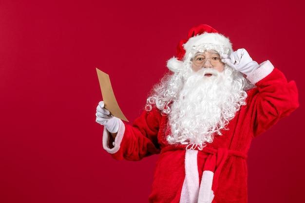 Widok z przodu święty mikołaj czytający list od dziecka na czerwonych świątecznych emocjach świątecznych