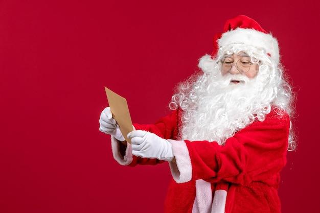 Widok z przodu święty mikołaj czytający list od dziecka na czerwonym biurku świąteczna emocja świąteczna