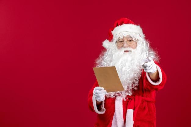 Widok z przodu święty mikołaj czytający list od dziecka na czerwonym emocji obecny świąteczny święta