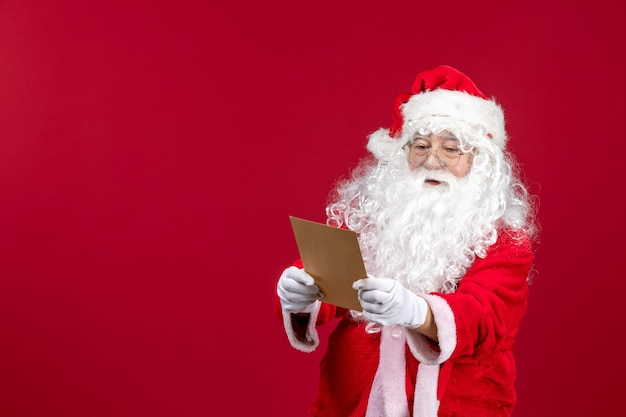 Widok z przodu święty mikołaj czytający list od dziecka na czerwonym emocji prezent świąteczny