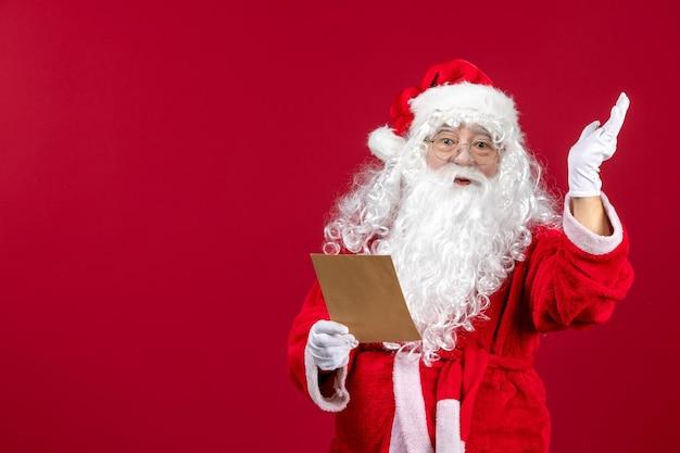 Widok z przodu święty mikołaj czytający list od dziecka na czerwonym prezenty świąteczne emocje