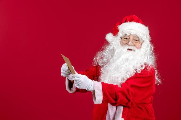 Widok z przodu święty mikołaj czytający list od dziecka o czerwonych świątecznych emocjach świątecznych