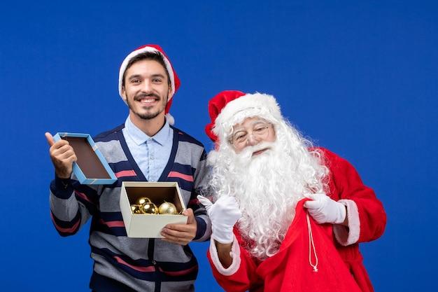 Widok z przodu święty mikołaj dający prezent młodemu mężczyźnie na niebieskich świątecznych emocjach świątecznych