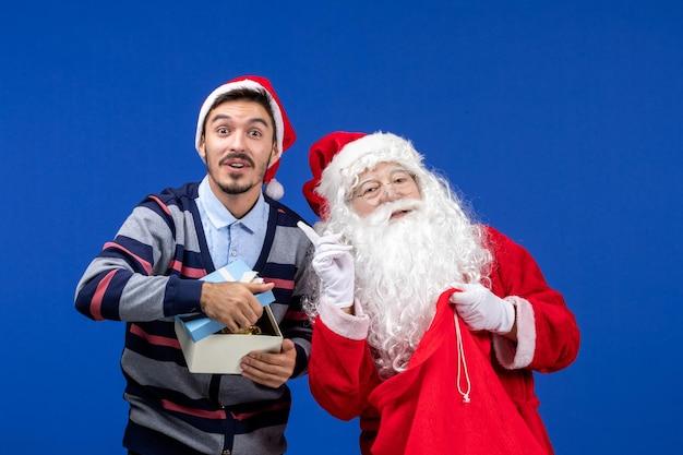 Widok z przodu święty mikołaj dający prezent młodemu mężczyźnie na niebieskim świątecznym święcie