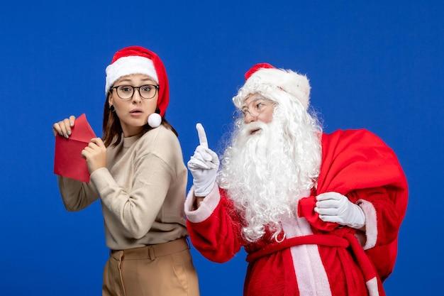 Widok z przodu święty mikołaj i młoda kobieta list otwierający na niebieskich wakacyjnych emocjach bożego narodzenia nowego roku