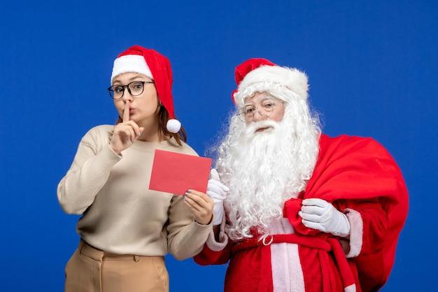 Widok z przodu święty mikołaj i młoda kobieta trzyma list na niebieskich świątecznych świątecznych emocjach kolorystycznych nowego roku