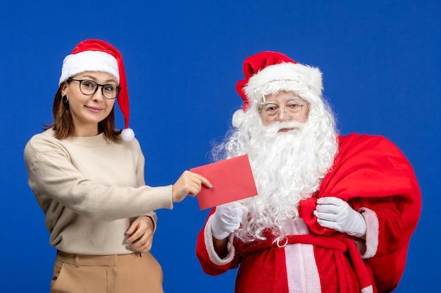 Widok z przodu święty mikołaj i młoda kobieta trzymająca list na niebieskich świątecznych świątecznych emocjach kolorystycznych