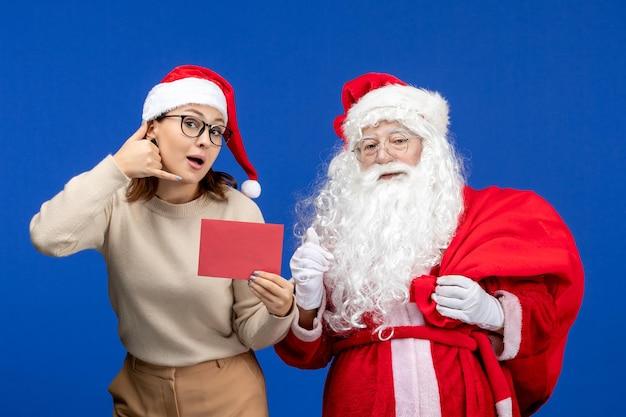 Widok z przodu święty mikołaj i młoda kobieta trzymająca list na niebieskich świętach boże narodzenie nowy rok kolor emocji