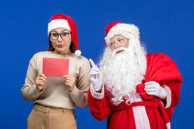 Widok z przodu święty mikołaj i młoda kobieta z literą na niebieskim świątecznym duchu emocja świąteczny kolor śniegu