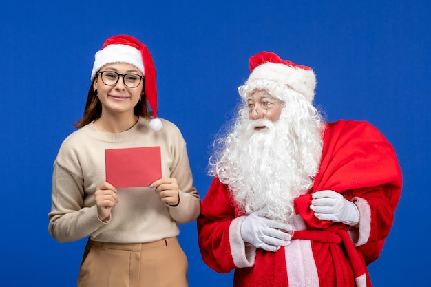 Widok z przodu święty mikołaj i młoda kobieta z literą na niebieskim świątecznym duchu emocja świąteczny śnieg