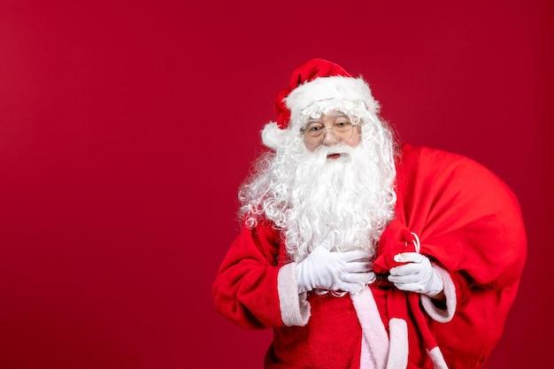 Widok z przodu święty mikołaj niosący czerwoną torbę pełną prezentów na czerwonej podłodze świąteczne emocje nowy rok