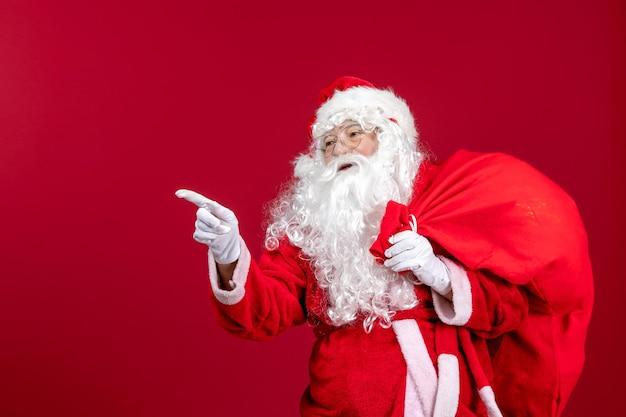 Widok z przodu święty mikołaj niosący czerwoną torbę pełną prezentów na czerwonych świątecznych emocjach nowy rok wakacje