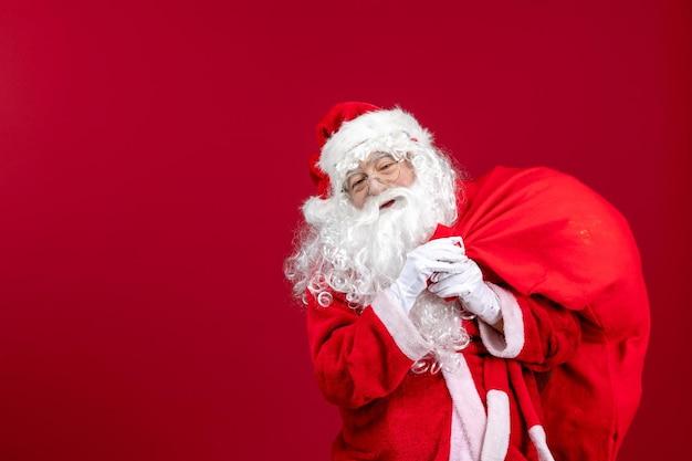 Widok z przodu święty mikołaj niosący czerwoną torbę pełną prezentów na czerwonych świątecznych emocjach święta nowego roku