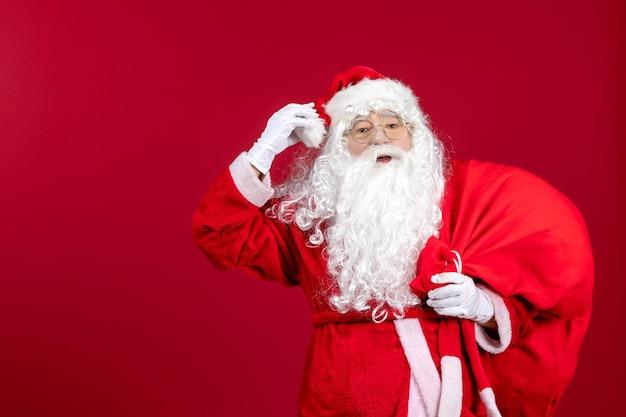 Widok z przodu święty mikołaj niosący czerwoną torbę pełną prezentów na czerwonym biurku świąteczne emocje nowy rok
