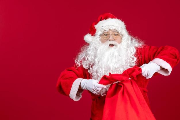 Widok z przodu święty mikołaj otwierający torbę pełną prezentów dla dzieci na czerwonej podłodze świąteczne emocje świąteczne