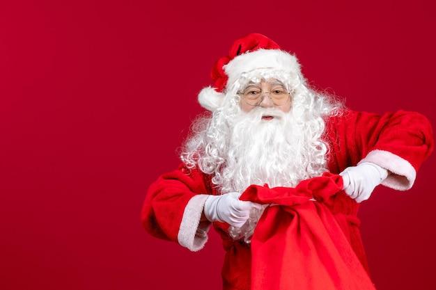 Widok z przodu święty mikołaj otwierający torbę pełną prezentów dla dzieci na czerwonym biurku świąteczne emocje świąteczne