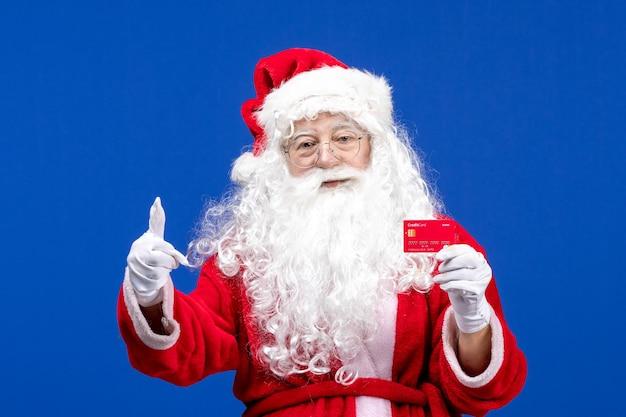 Widok z przodu święty mikołaj trzymający czerwoną kartę bankową na niebieskim świątecznym kolorze w nowym roku