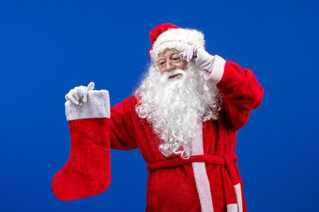 Widok z przodu święty mikołaj trzymający dużą skarpetę świąteczną na niebieskim biurku w kolorze świątecznym śniegu