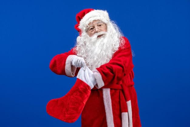 Widok z przodu święty mikołaj trzymający dużą skarpetę świąteczną na niebieskim kolorze podłogi świąteczny śnieg