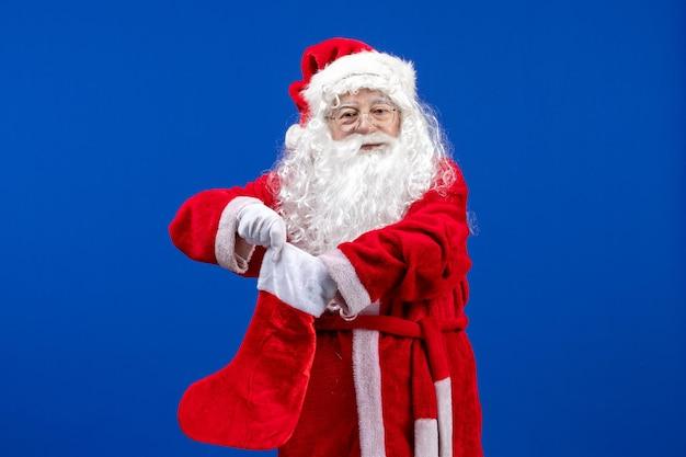 Widok z przodu święty mikołaj trzymający dużą skarpetę świąteczną na niebieskim kolorze świątecznym śniegu