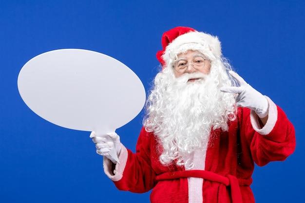 Widok z przodu święty mikołaj trzymający duży biały znak na niebieskim biurku śnieżny świąteczny kolor boże narodzenie